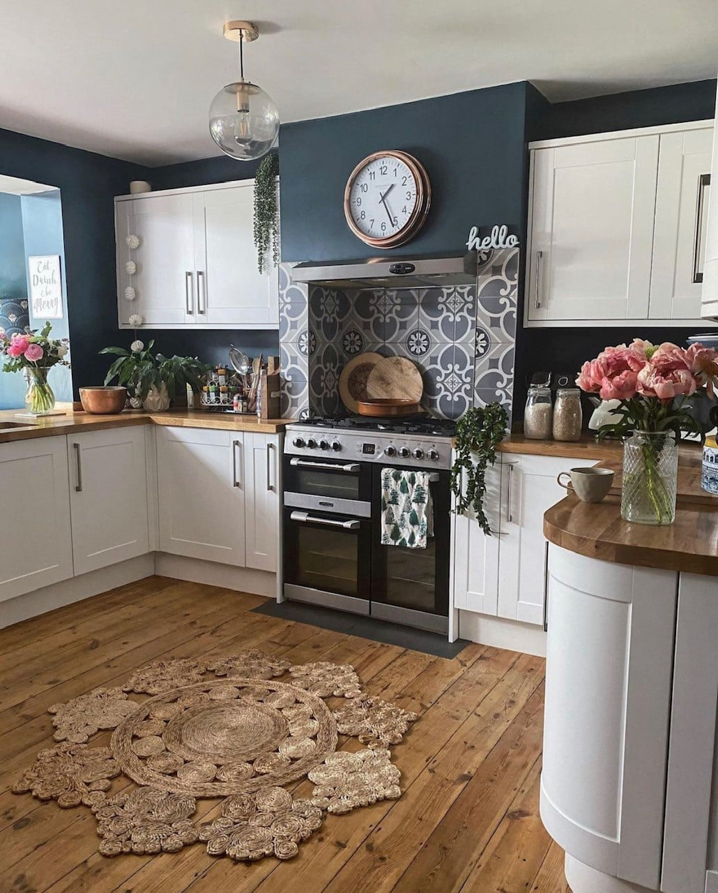 Newly renovated kitchen with wooden floors, range cooker in the chimney, hague blue farrow and ball walls, howden kitchen, tiled back splash and jute rug