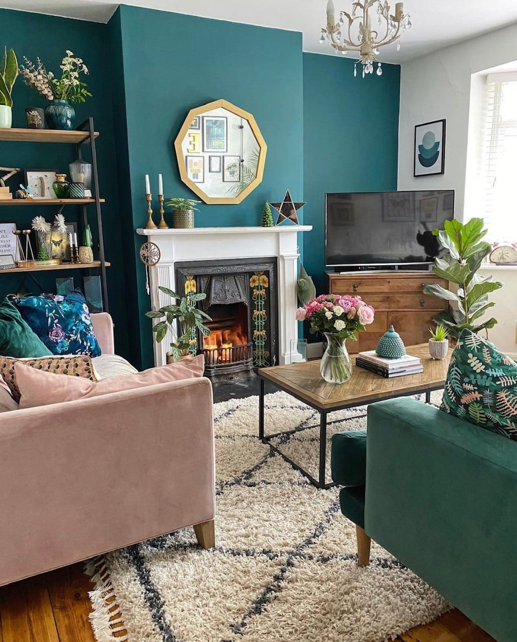 Blue jade wall in the living room with green velvet and pink velvet sofas, industrial style coffee table, fireplace and large white rug