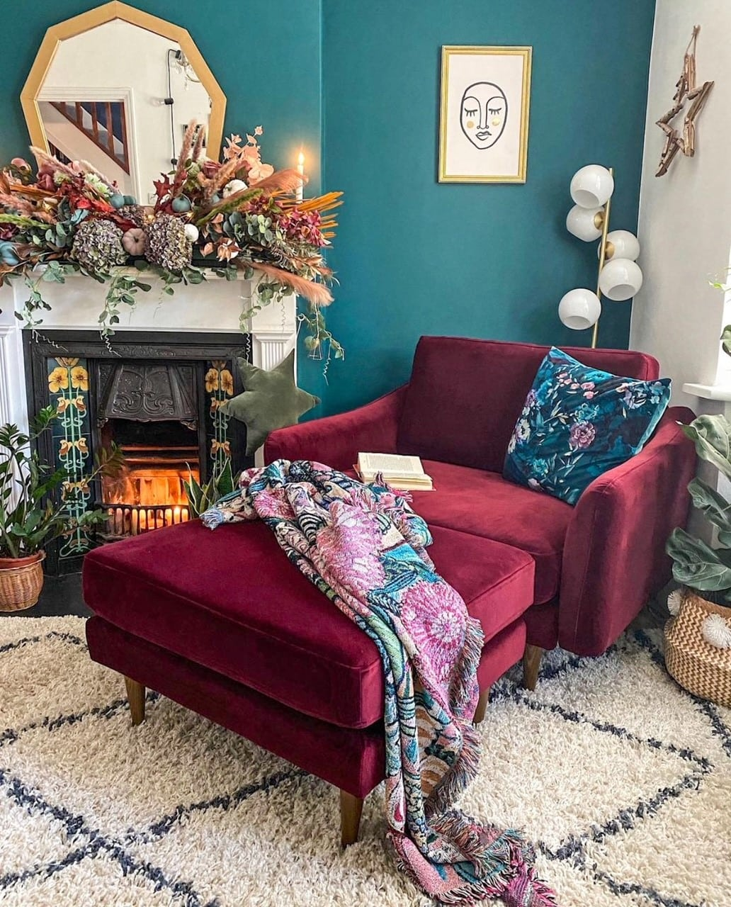 red velvet sofa, green walls and fireplace in the living room