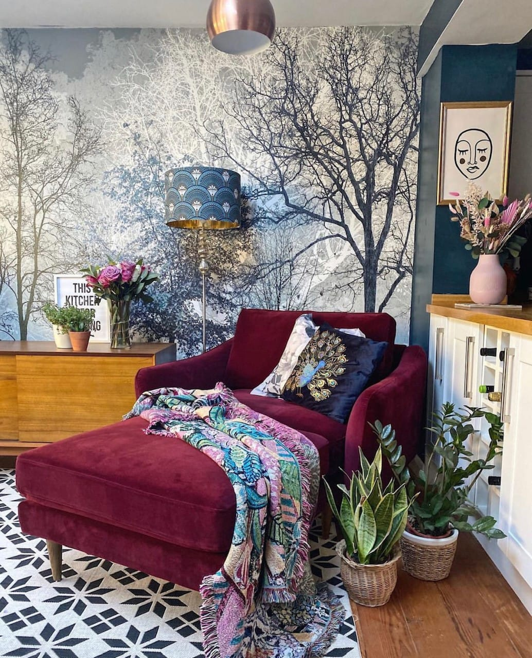 mulled wine deep burgundy velvet sofa in the kitchen diner with forest wallpaper mural, mid century furniture and ikea rug