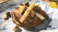 Een gestapeld torentje van kleine pannenkoekjes gemaakt van ei en banaan met raaover stukjes appel en wat nootjes