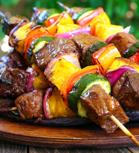 grilled steak kabobs with pineapple and vegetables on a platter