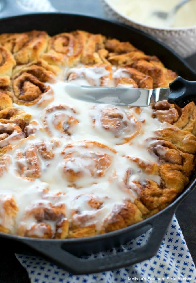 frosting cinnamon rolls in a skillet