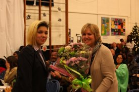 Molly presenting a bouquet to the Head Teacher Alexandra Hardy.
