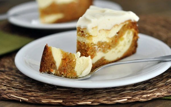 A piece of carrot cake cheesecake, with a bite taken out on a white plate.