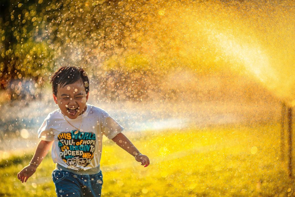 A small child laughing joyfully while running through a sprinkler.