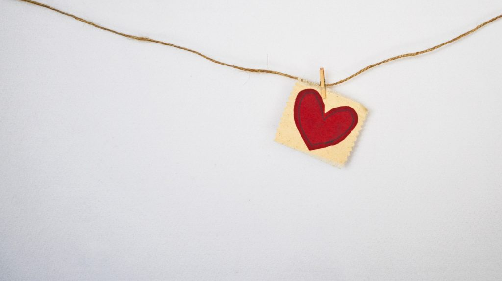 a heart painted on a card, positioned against a  large white background