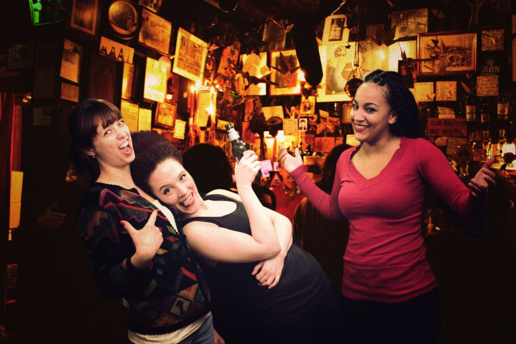 Lauren A. Kennedy, Sarah Schoofs, and Rory Lipede as Lesley, Jennifer, and Andrea in a group shot in a bar that appears in the background of scenes in Lesley and Andrea's apartment.