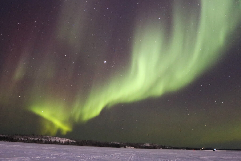 Purple and green Northern Lights dance over Yellowknife, Canada