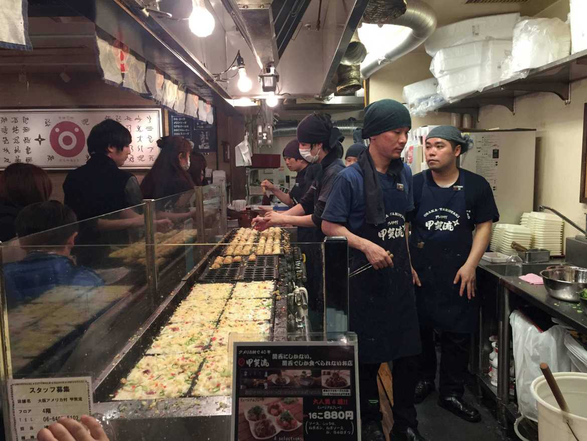 Cooks preparing takoyaki in Osaka, Japan