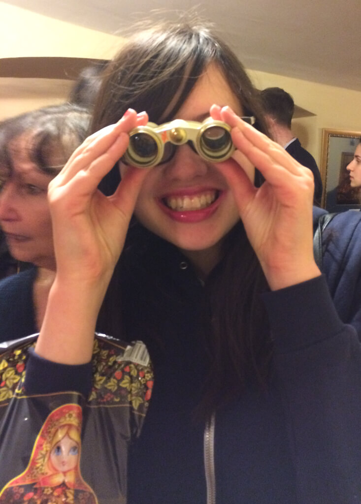 A girl using opera glasses in St. Petersburg, Russia