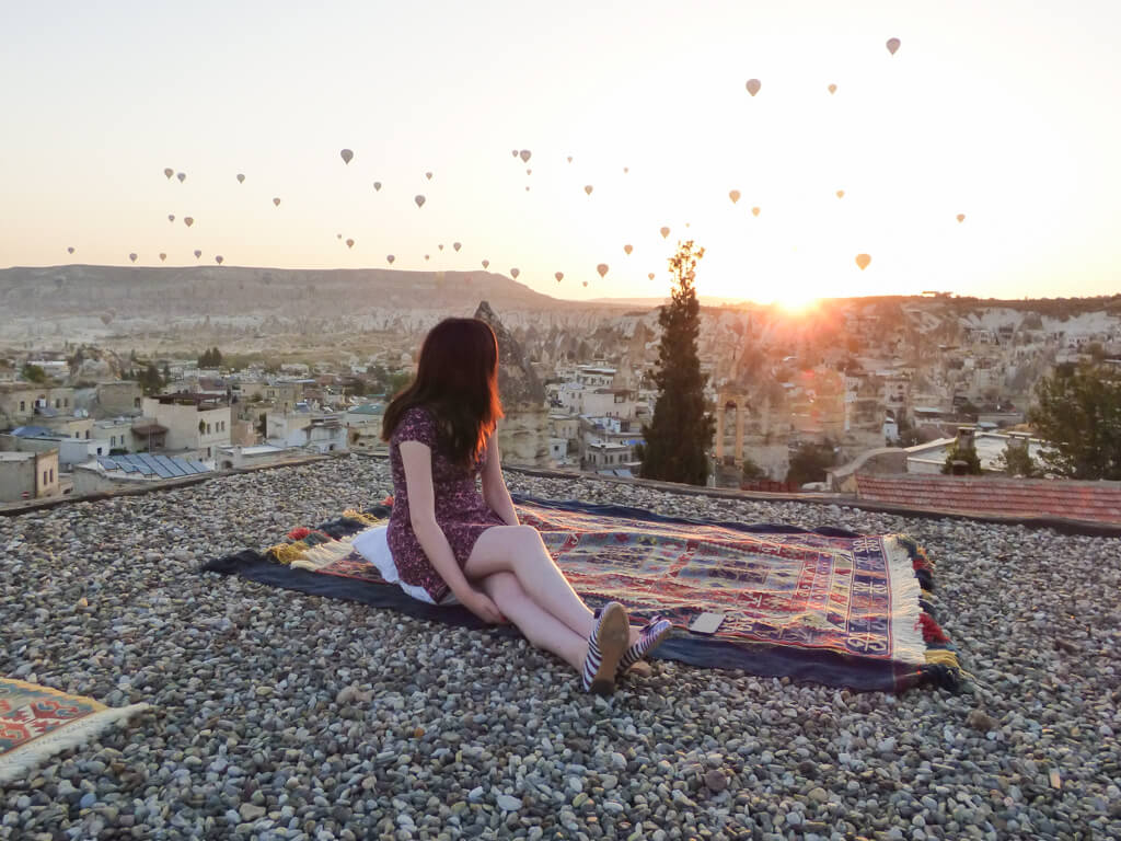 A girl watches the sunrise from the roof of Sultan Cave Suites