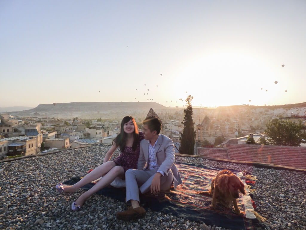 A couple sitting on a rug watching the sunrise next to a puppy