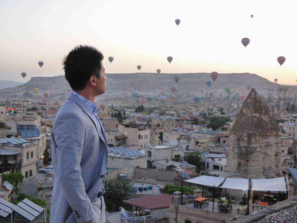 A man watches hot air balloons from the roof of Sultan Cave Suites