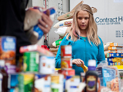 Girl helping with food donations