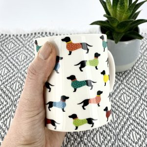 Our adorable bone china dachshund mug features a repeat pattern of small Dachshunds all the way around the mug.