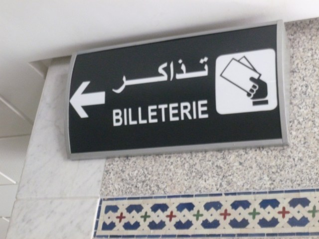 Signs written in both Arabic and French point to the ticket area as you enter Gare Rabat Ville