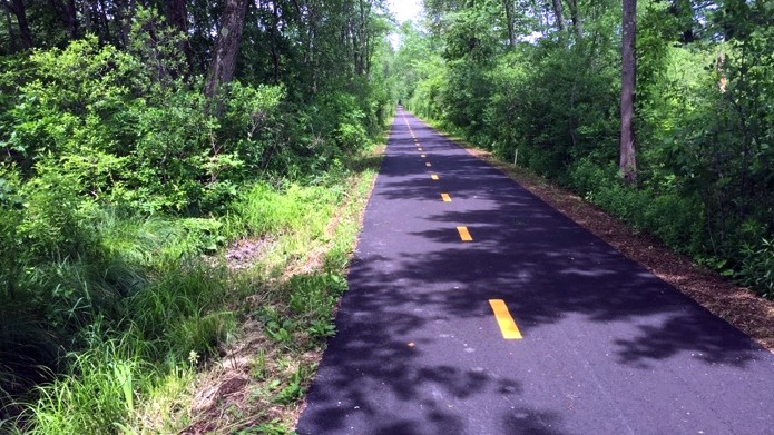 The Norwottuck Rail Trail heading towards Amherst from Warren Wright Road in Belchertown, MA.