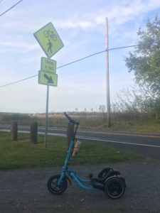 Blue Me-Mover next to trail crossing sign with farmland in the background