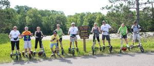 Ten Trikke riders pose for a group photo along side signage for the Paul Bunyan State Trail and Heartland State Trail