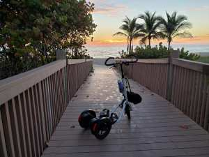 White Me-Mover on a boardwalk looking towards a beach at sunrise