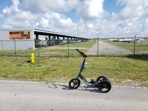 Teal Me-Mover Touring prototype in front of a hangar of small airplanes