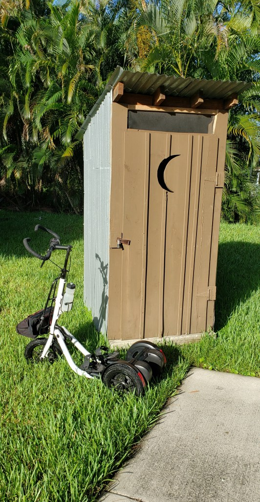 White Me-Mover parked in front of a tan outhouse with a crescent moon carved into the door