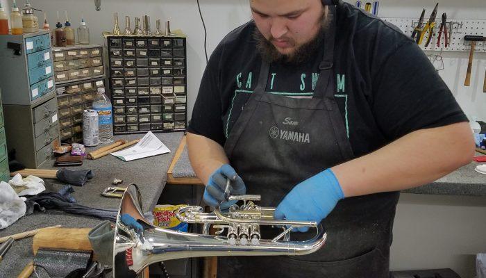 Repair tech repairing a silver trumpet