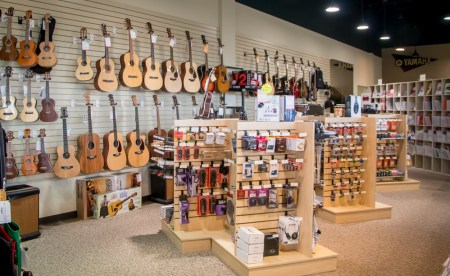 Guitars on wall display and other music products on smaller displays.