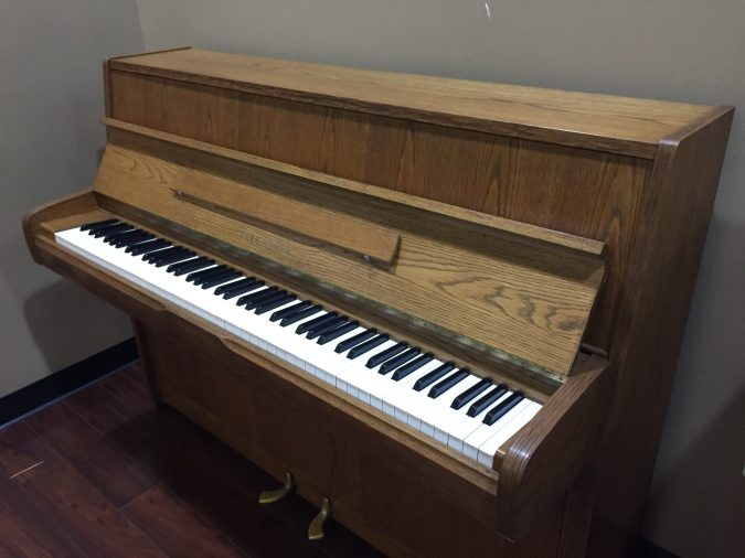 Side view of Young Chang upright piano in oak with black and white piano keys