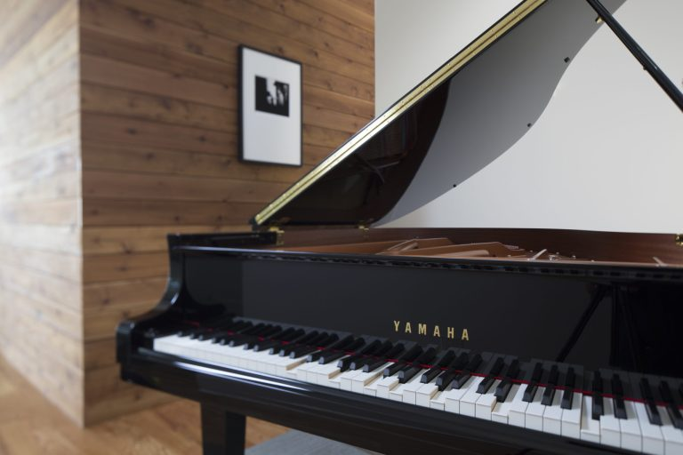 Yamaha Disklavier grand piano in front of white wall