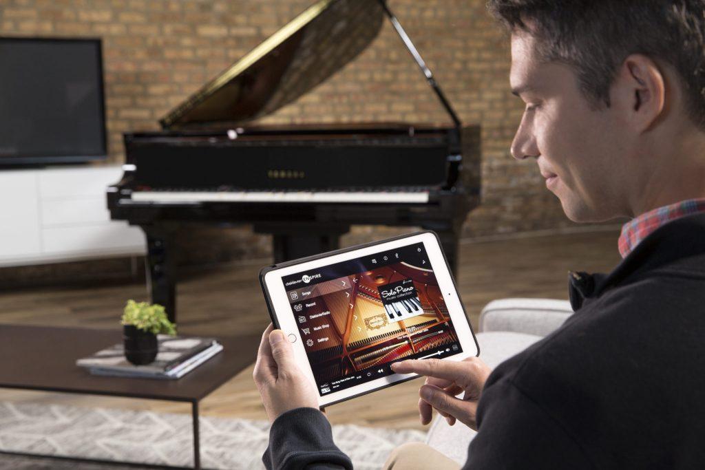 Man using Ipad to operate Yamaha Disklavier piano
