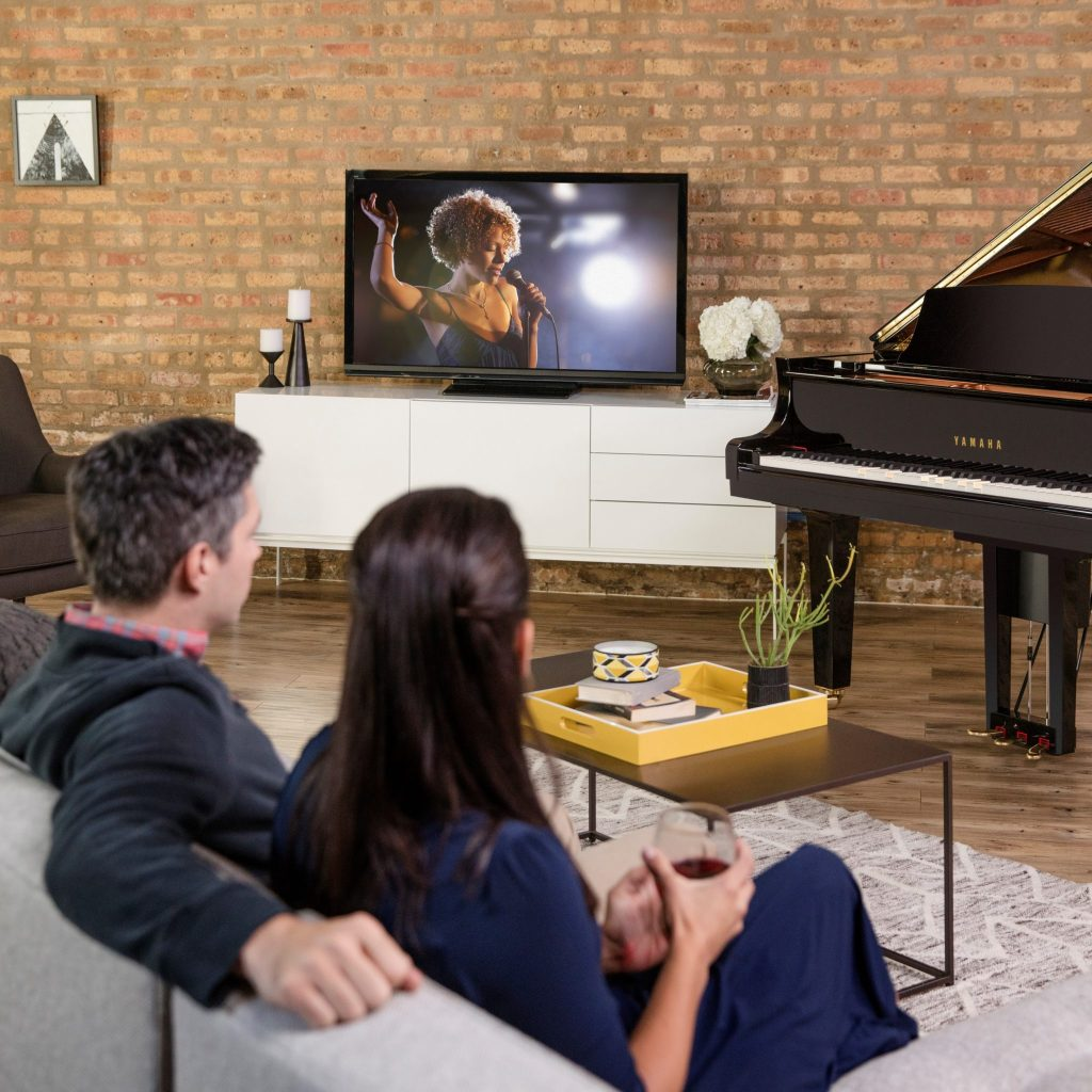 couple sitting on couch watching Yamaha Disklavier TV