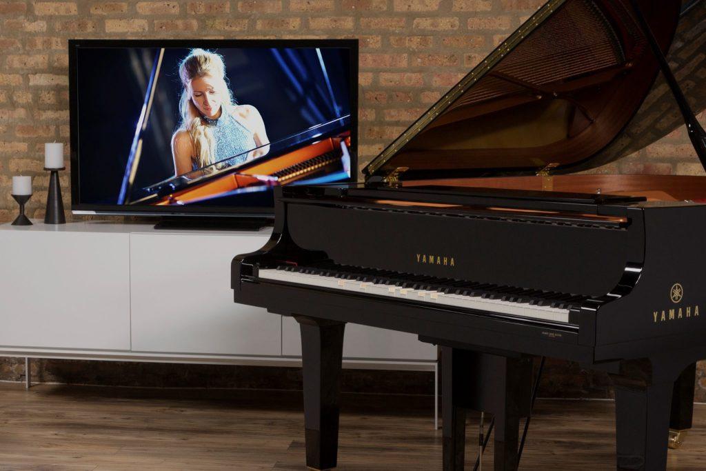 Yamaha Disklavier grand piano in front of brick wall