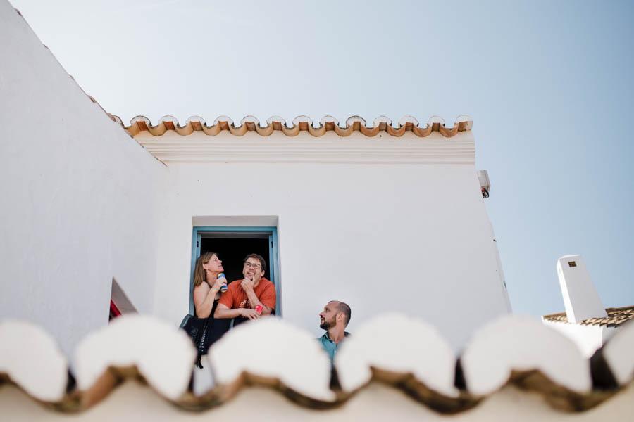 casamento aldeia de pedralva noivo conversa com amigos à janela de casa algarvia com telhados