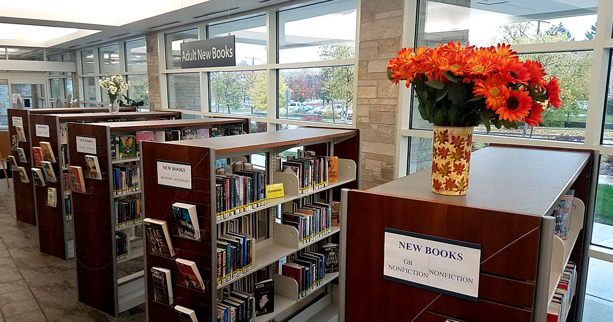 A vase of orange flowers on the new book shelves at the Library