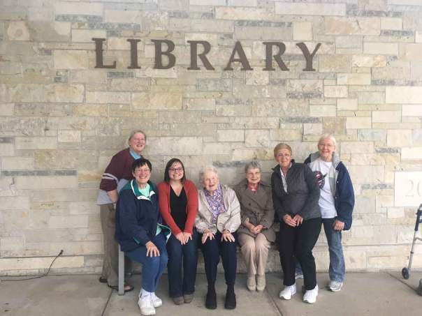Several members of the Library Friends, including Rightie Pappenheim, sitting on Rightie's bench