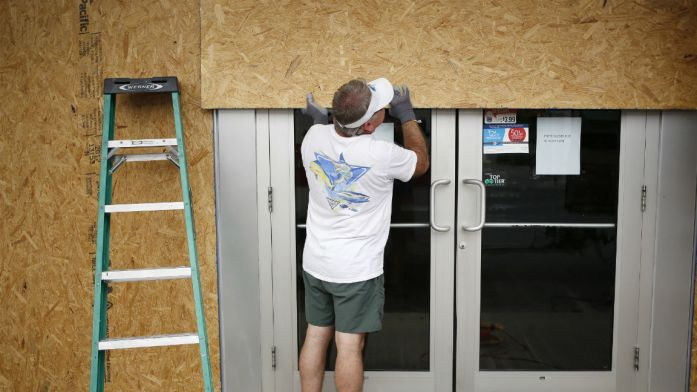 A worker boards up a gas station ahead of Hurricane Michael in Panama City Beach, Florida, U.S., on Tuesday, Oct. 9, 2018. Michael, a Category 2 hurricane, is racing toward the Florida panhandle and is forecast to become thesecond stormto make U.S. landfall in a month. Photographer: Luke Sharrett/Bloomberg via Getty Images