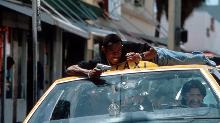 Martin Lawrence riding on the roof of a taxi while aiming a gun in a scene from the film 'Bad Boys', 1995. (Photo by Columbia Pictures/Getty Images)