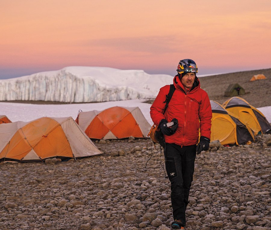 Will Gadd walking way from orange tents with iceberg in the distance