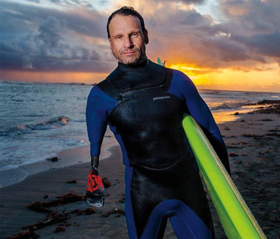 Portrait of Jeff Denholm holding surfboard against a sunset