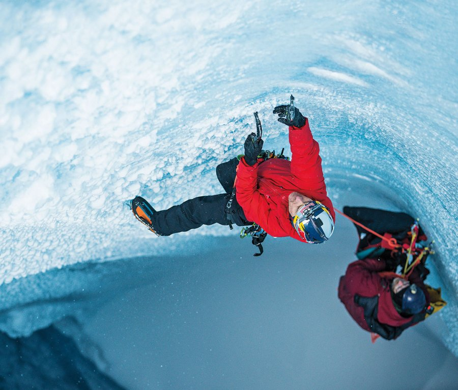 Will Gadd ice climbing in Greenland in bright red jacket