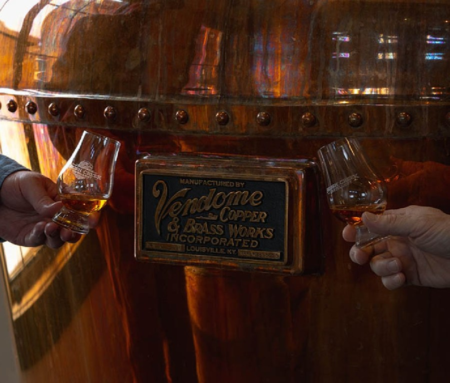 Two hands holding Brush Creek whiskey in front of a large copper still.