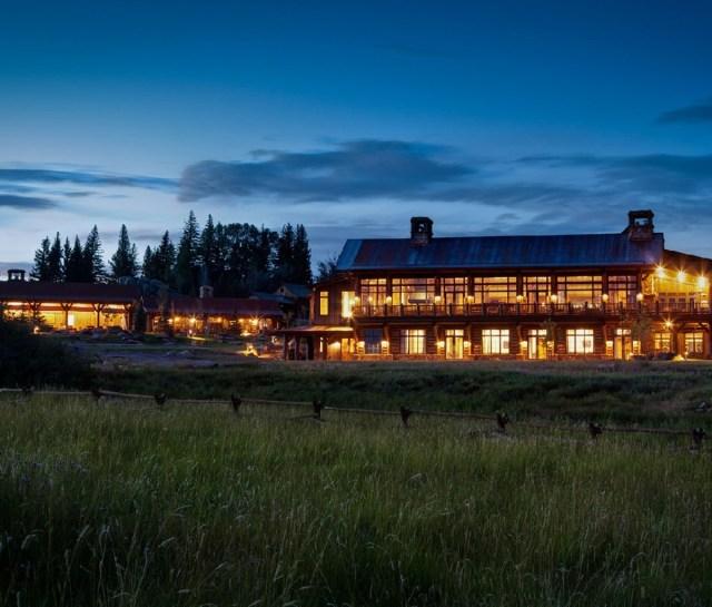 Een nachtelijk uitzicht op The Lodge & Spa op Brush Creek Ranch. Hoog gras is op de voorgrond, de lichten zijn allemaal aan in de Lodge.