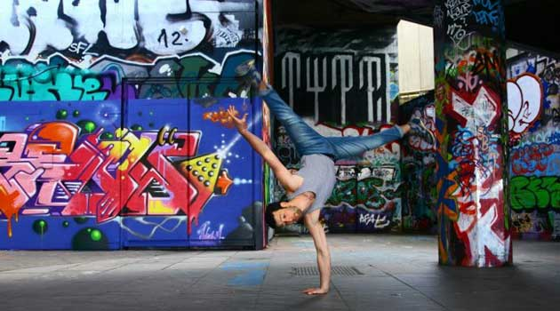 Guy showing of his athletic skills in front of grafitti