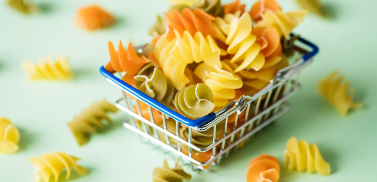 Dried pasta pieces in a tiny shopping basket