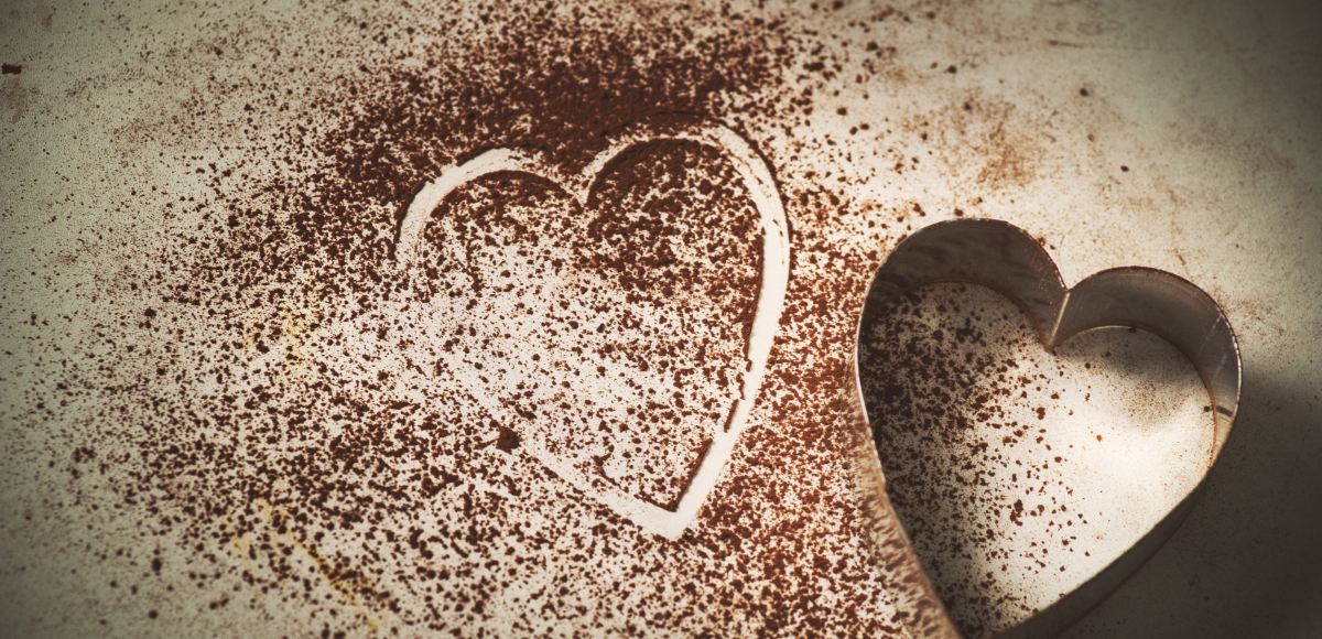 Heart shaped cookie cutter on counter with cocoa powder