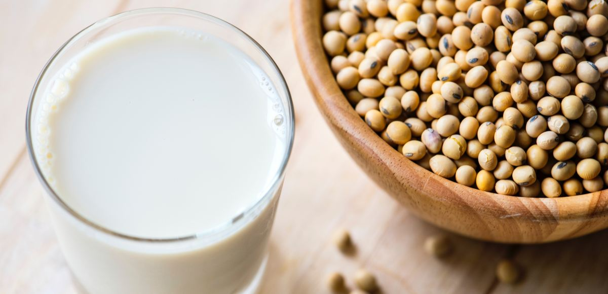 Glass of calcium rich soy milk and bowl of soy beans