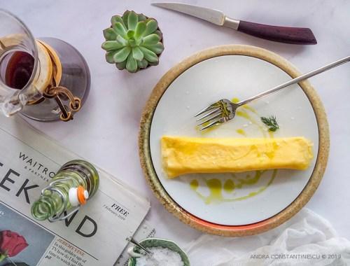 Mic dejun cu omleta japoneza in straturi servita pe o farfurie alba. Alaturi se afla o cafetiera si o sticla cu ulei de masline.