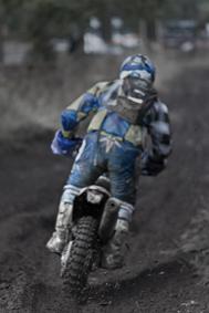 A motorcross bike is spraying dirt from a spinnings back wheel. Sweden.